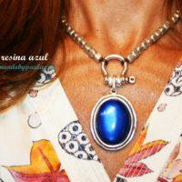 Collar con resina colgante azul y cubos de zamak bañados en plata.