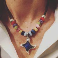 Collar corto con colgante de estrella y resinas de colores.