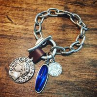 Pulsera con cadena clásica bañada en plata, con resina en color azul y cuero...